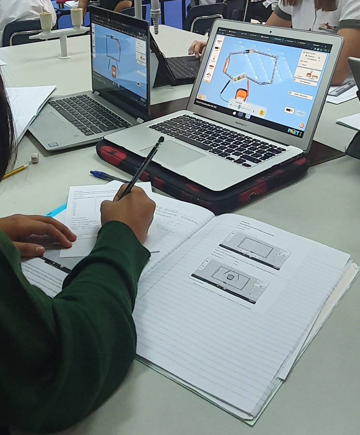 Students in class using devices to learn and writing in books